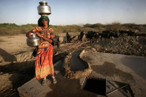 Una mujer recoge agua de un pozo provisional en India.| Ap