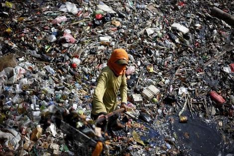 Un trabajador recolecta basura en un río contaminado de Yakarta (Indonesia). | Mast Irham/Efe