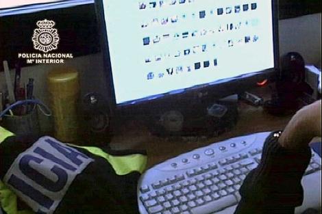 Un agente estudia material intervenido en una operación contra la pederastia. | Interior