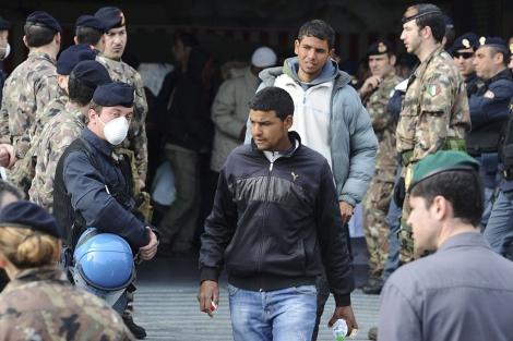 Inmigrantes procedentes de Lampedusa desembarcan de un buque militar en Nápoles. | Efe