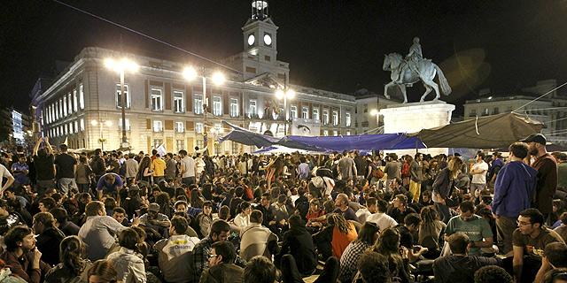 Los manifestantes de la Puerta del Sol se preparan para pasar la noche en la plaza.   Efe VEA MÁS IMÁGENES