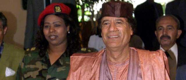 Muamar Gadafi con una de sus guardaespaldas. | Ap