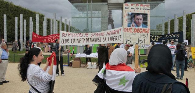 Una mujer sostiene una pancarta que pide la salida de Assad. | Afp