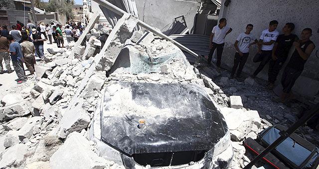 Varios ciudadanos contemplan los destrozos causados por el ataque de la OTAN en Trípoli. | Efe