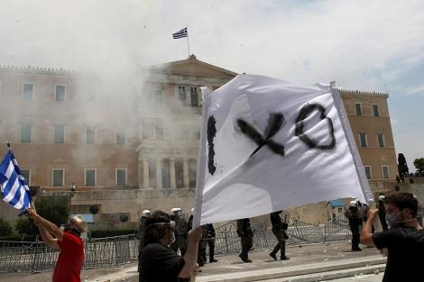 Manifestantes ondean una pancarta en la que se lee 'No' frente al Parlamento. | Efe