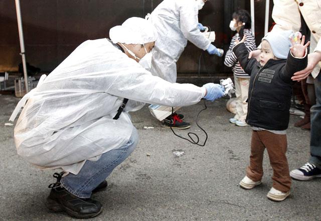 Un técnico mide la radiactividad externa a un niño en las inmediaciones de Fukushima tras el accidente. | Reuters