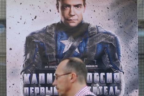 Un hombre pasa por delante de un cartel que muestra a Medvedev vestido de superhéroe. | Afp