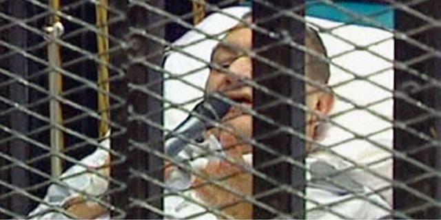El ex presidente Hosni Mubarak, en una camilla y detrás de las rejas durante el juicio. | Afp