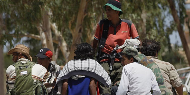 Combatientes libios rebeldes se reúnen en un puesto de control cerca de Bir Shuaib. | Reuters