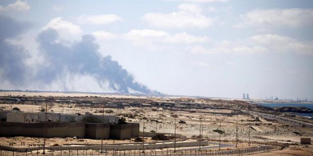 Una columna de humo negro sale desde el centro petrolero de Brega. | AP