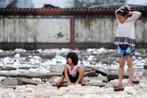 Dos niñas juegan en las calles de Pekín tras quedarse sin escuela, que fue demolida. | Afp