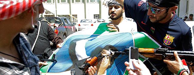 Un grupo de rebeldes destroza una foto de Gadafi en Trípoli. | Ap