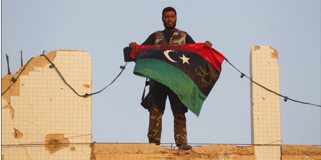 Un rebelde agita la bandera libia en el interior del complejo residencial de Gadafi. | Reuters
