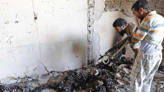 Rebeldes contemplan los cadáveres carbonizados de insurgentes a las afueras de Trípoli. | Efe