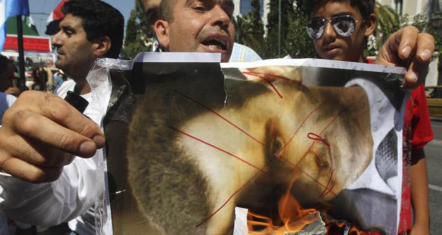 Manifestantes sirios residentes en Atenas queman retratos del presidente Bashar Asad. | Efe