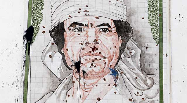 Un retrato acribillado del depuesto dictador libio Muamar Gadafi, en una calle de Trípoli, la capital del país árabe. | Reuters