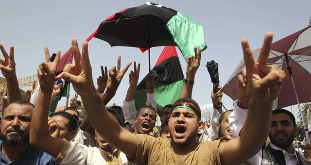 Decenas de hombres gritan consignas tras las oraciones de este viernes en la Plaza de los Mártires de Trípoli. | Efe