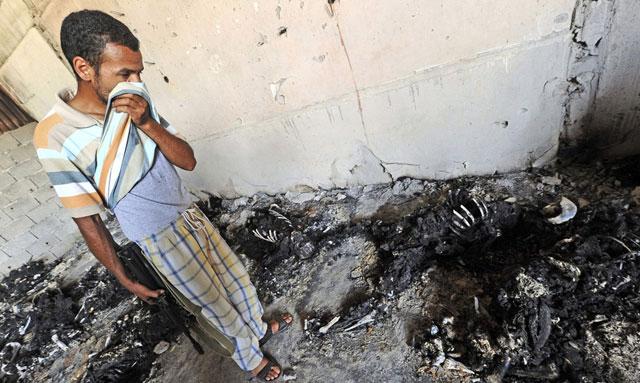 Un hombre se tapa la nariz, frente a decenas de cadáveres quemados. | Efe