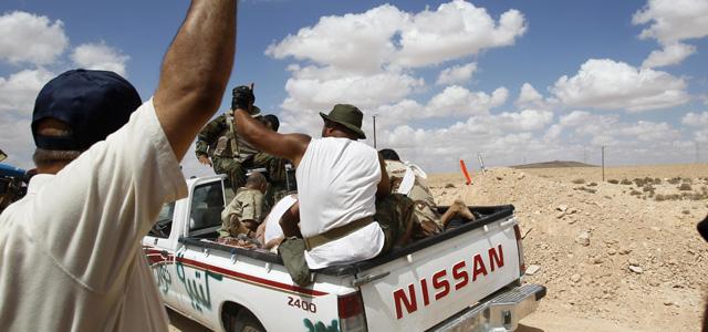 Rebeldes libios transportan a un grupo de gadafistas apresados a las afueras de Bani Walid. | Reuters