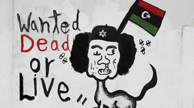 Una caricatura de Gadafi junto al rótulo 'Se busca vivo o muerto', en Trípoli. | Efe