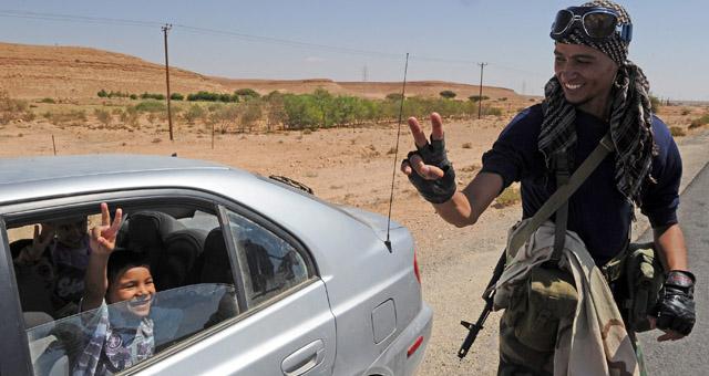 Un rebelde saluda a un niño con gesto de victoria en un puesto de control cerca de Bani Walid. | Efe