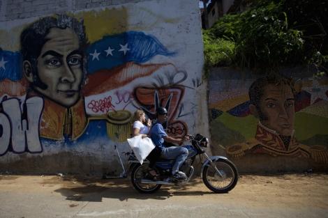 Una pareja pasa ante unos retratos de Simón Bolívar en Caracas. | Reuters