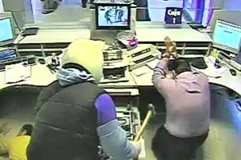 Uno de los atracadores amenaza al encargado de la caja de una sucursal..