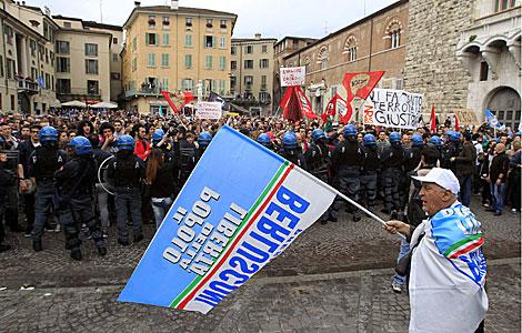 Un partidario de Berlusconi, mientras la policía bloquea a sus detractores.   Reuters