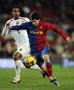 Messi se lleva el balón ante la persecución de Cléber Santana. (AFP)
