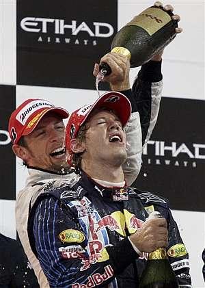 Sebastian Vettel, 'bañado' en el podio por Jenson Button. (AP)