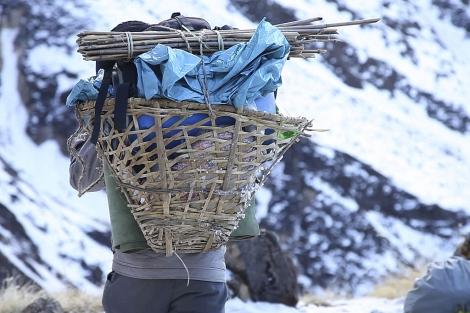 Un porteador muestra de espaldas el cesto de bambú con el que carga materiales.