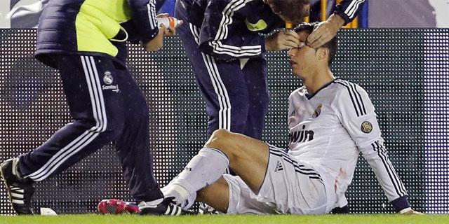 Cristiano Ronaldo, atendido en la banda tras el codazo de David Navarro. (EFE)
