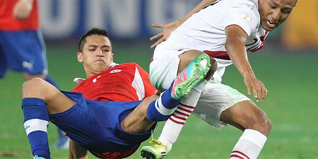 Alexis Sánchez, frente a Alberto Ramírez, en el último partido en Perú. (Foto: Efe)