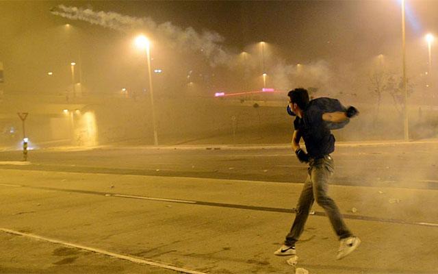 Uno de los manifestantes lanza una lata de gas lacrimógeno en Belo Horizonte. | Afp