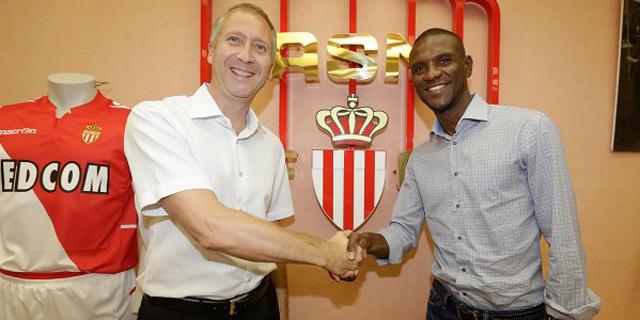 Abidal le da la mano a un representante del Mónaco con el escudo de la entidad de fondo. | Mónaco F.C.