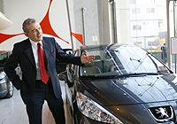 El presidente de PSA Peugeot-Citröen, Christian Streiff, posa junto a un modelo de la firma.