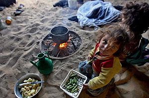 Unas niñas palestinas comen en una chabola en Al Zitun, Gaza. (Foto: Ali Ali | EFE)