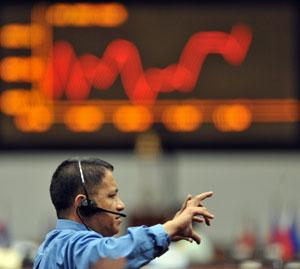 Un financiero gesticula ante una pantalla con uno de los índices económicos en Manila. (Afp)