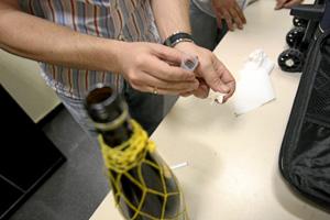 Un guardia civil toma una muestra de una botella de ron para saber si lleva cocaína disuelta. (Foto: Carlos Miralles)