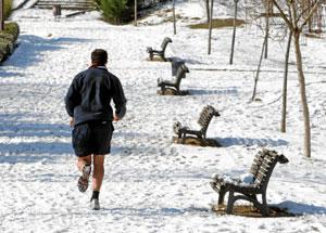 Un hombre hace footing en un parque nevado. (Foto: Carlos Espeso)