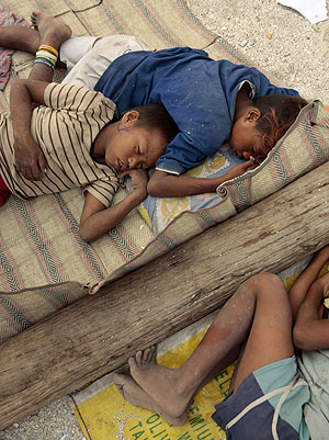 Niños filipinos descansan durante su dura jornada de trabajo, con la que ayudan a sus familias. (EFE)