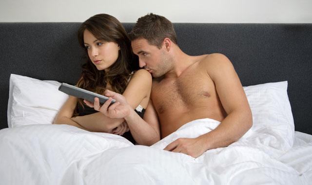 Un hombre besa a su pareja en la cama. | Nigel Riches
