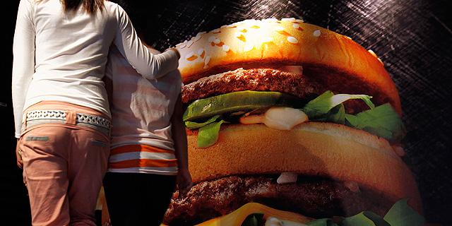 Una madre y su hija pasean por la calle ante el cartel de una hamburguesa