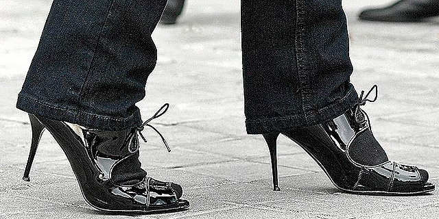 Pies de mujer calzados con zapatos de tacón alto.