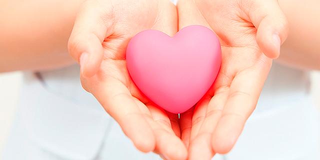 Unas manos de mujer sostienen un corazón de goma.| EM