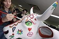 Una artista pinta una vaca durante la presentación de la 'Cow Parade' madrileña. (Foto: EFE)
