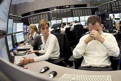 Varios agentes hacen un gesto de preocupación en la Bolsa de Fráncfort. (Foto: EFE)