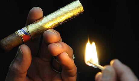 Un participante en la feria enciende un puro 'de oro'. (Foto: AP)